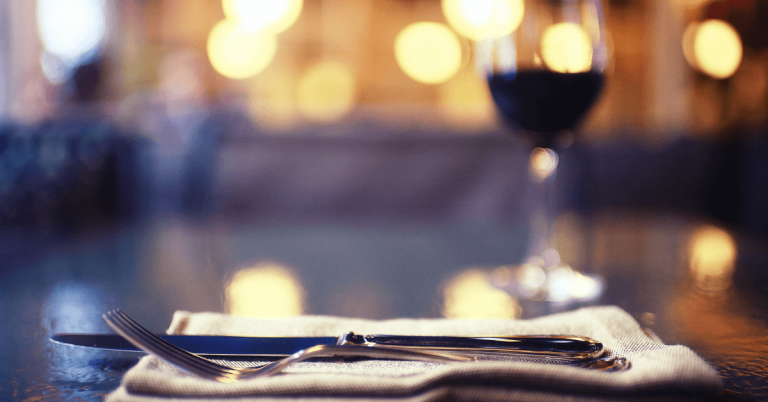 fork knife and napkin place setting with a glass of red wine on a restaurant table
