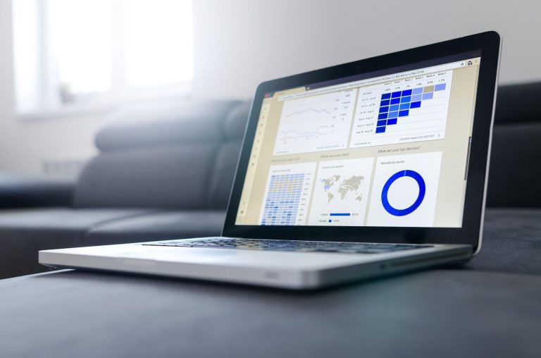 image of a laptop with an analytics dashboard pictured on the screen