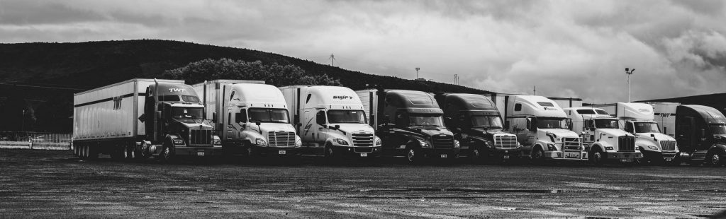 grey scale image of several semi trucks lined up next to each other in a parking lot