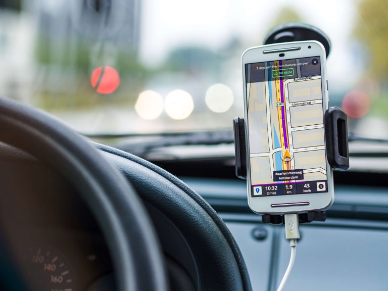 GPS displayed on a smartphone inside a vehicle next to the steering wheel
