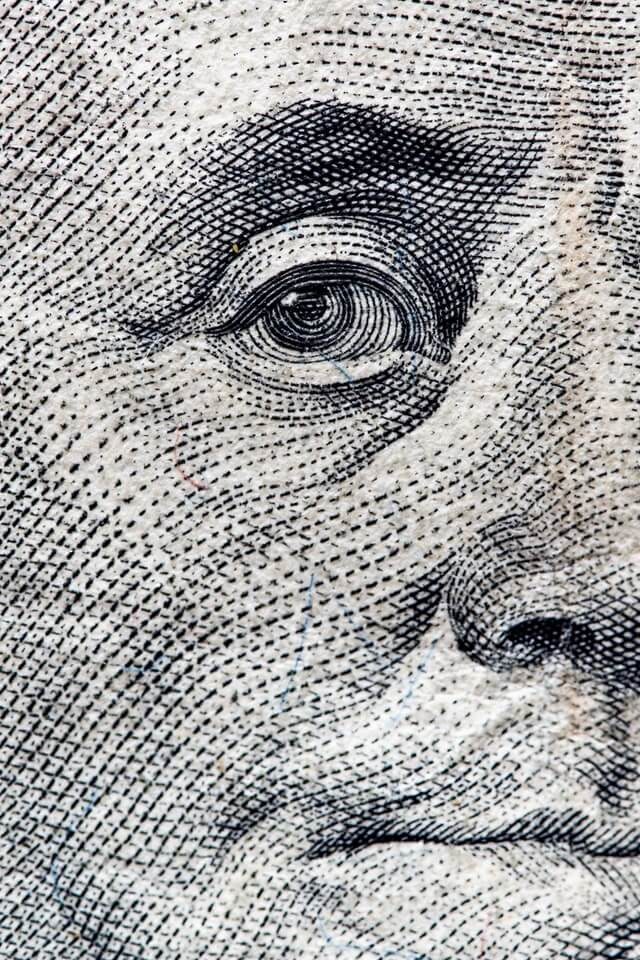 close up view of Benjamin Franklin's face depicted on the one hundred dollar bill
